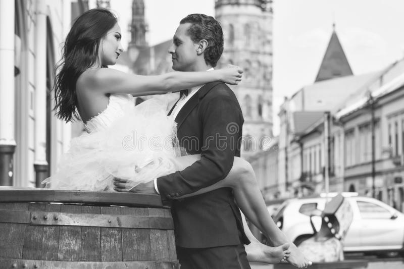 Wedding couple on wooden barrel near castle. Young wedding couple of girl with brunette hair and pretty face in white bride dress sitting on wooden barrel and stock images