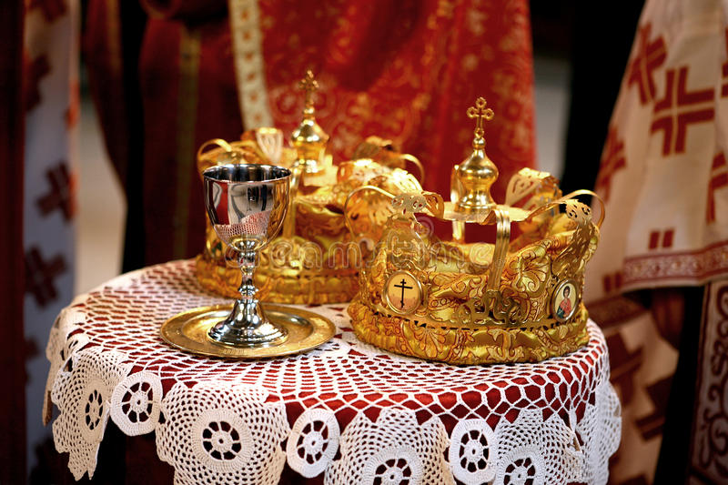 Wedding crowns. Two wedding crowns and a cup on a table in orthodox church royalty free stock photos