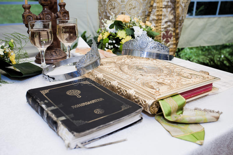 Wedding crowns, bible and wine glasses. Prepared for ceremony stock images