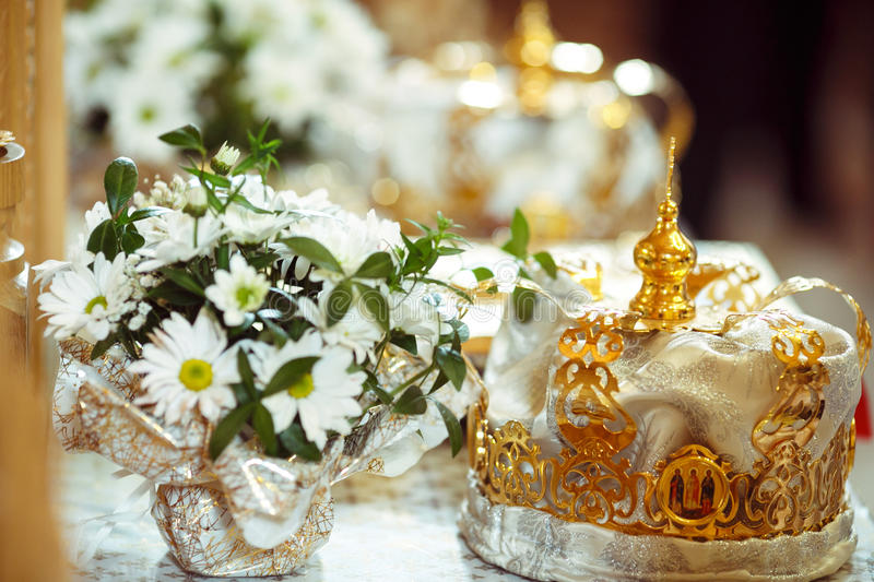 Wedding crowns stand behind a bouquet of chamomiles.  stock photography