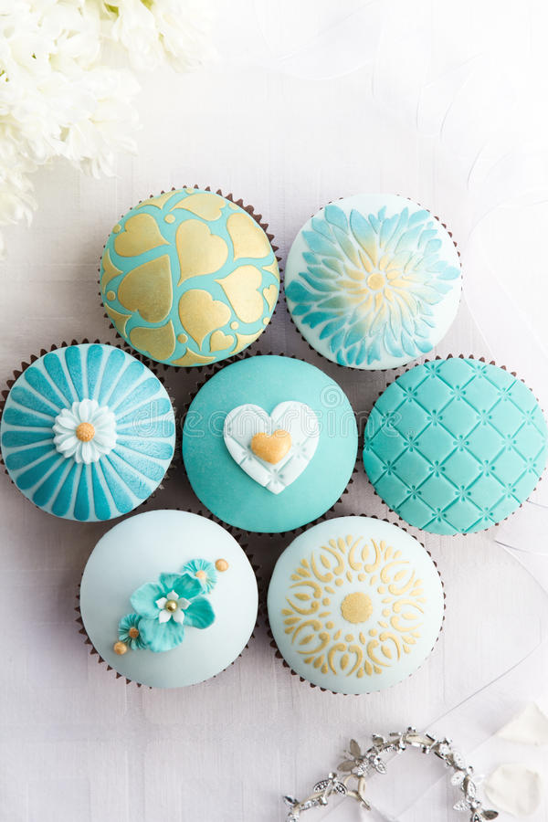 Wedding cupcakes. In turquoise and gold royalty free stock photo