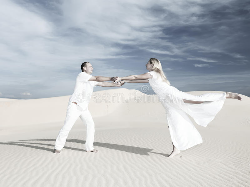 Wedding dance. Young couple dancing on desert dune at wedding date royalty free stock images