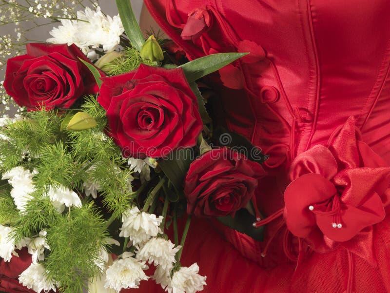 Wedding day. Red roses on scarlet wedding dress stock image