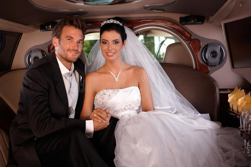 Wedding-day. Bride and groom sitting happily in limo on wedding-day stock photography