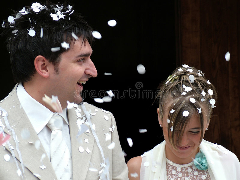 Wedding day. A wedding, bride and groom walking out of church after ceremony into a rain of rice and confetti from guests royalty free stock image