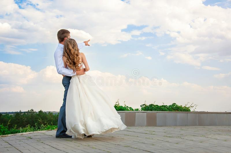 Wedding Day. Beautiful Bride in the Arms of the Groom on Sky Background.  royalty free stock photo