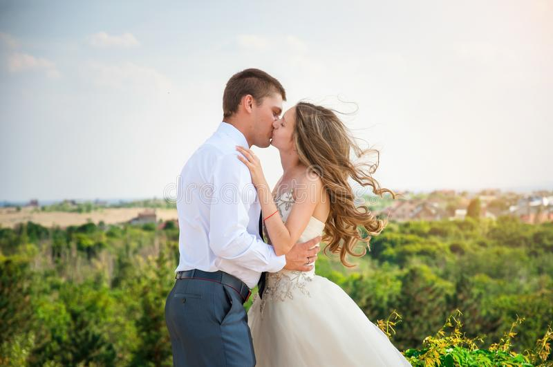 Wedding Day. Beautiful Bride in White Dress with Groom. Happy Kissing Couple stock image