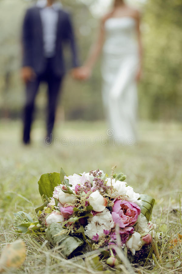 Wedding day, bouqet with peonies, couple defocused royalty free stock photography