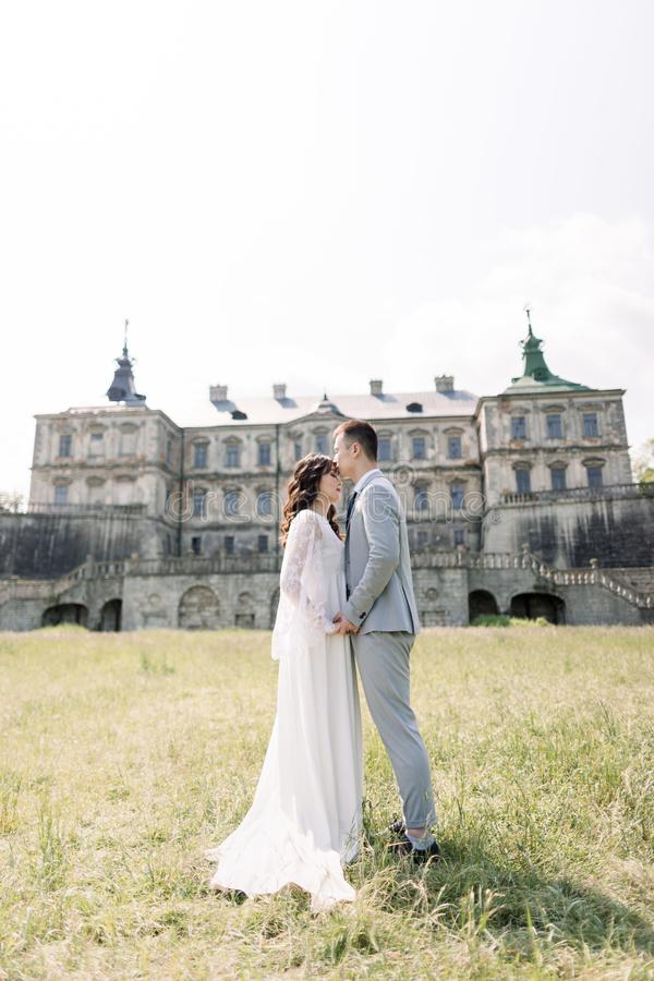 Wedding day. Bride and groom, Chinese couple, walking near an old castle, holding hands and hugging stock images