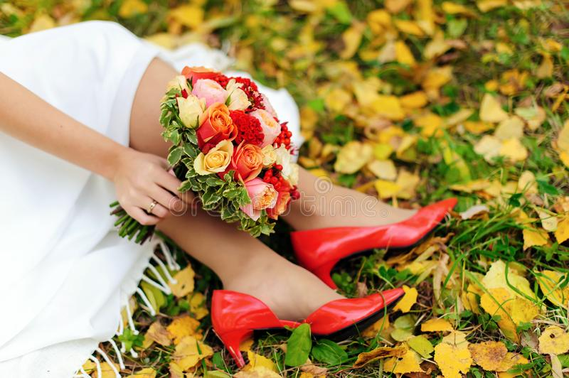 Wedding day. Close up of bride`s feet in red shoes, colorful bridal bouquet and autumn leaves on green grass royalty free stock photography
