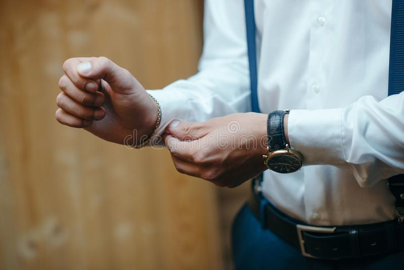 Handsome happy groom putting on stylish white shirt before wedding, confident businessman preparing for meeting, morning wedding p. Wedding day. Handsome happy stock photography