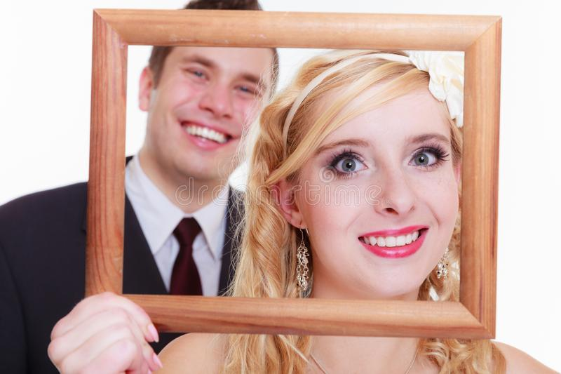Groom and bride holding empty frame. Wedding day, positive relationship concept. Groom and bride holding, posing with empty photo frame royalty free stock photos