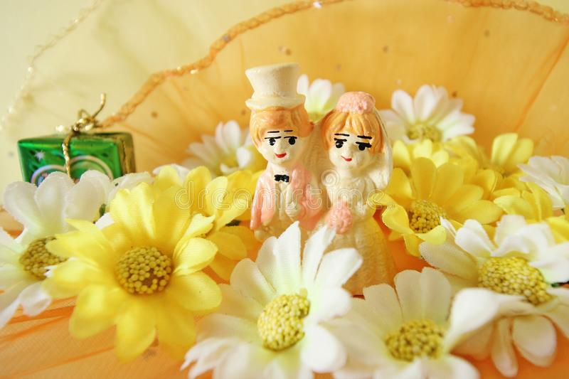 Wedding Day or wedding anniversaries concept. With Wedding dolls and flowers on vintage background, soft focus royalty free stock photography