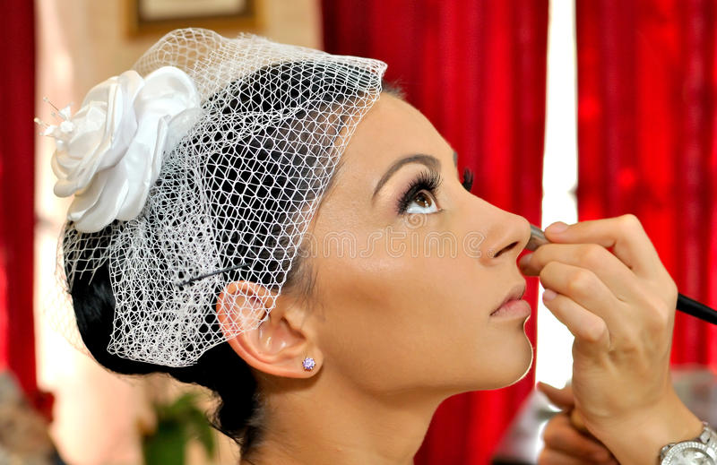 Wedding day. A young bride, having her make-up in the wedding day stock image