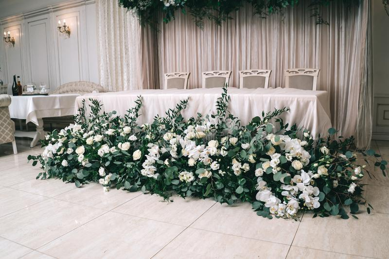 Wedding decor, accessories, orchids, roses, eucalyptus, a bouquet in a restaurant, chairs table setting royalty free stock images