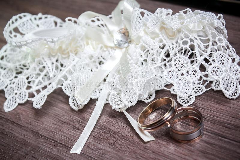 Wedding. Decor. Bride`s shoes, a beautiful wedding bouquet, rings, boutonniere and jewelry are beautifully laid out on a stock photos