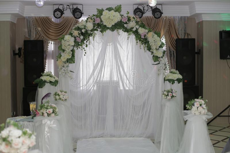Wedding arch, decorated with flowers, musical speakers and searchlights in the background royalty free stock images
