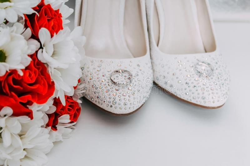 Wedding decor, details of the morning of the bride. White shoes in rhinestones and wedding royalty free stock image