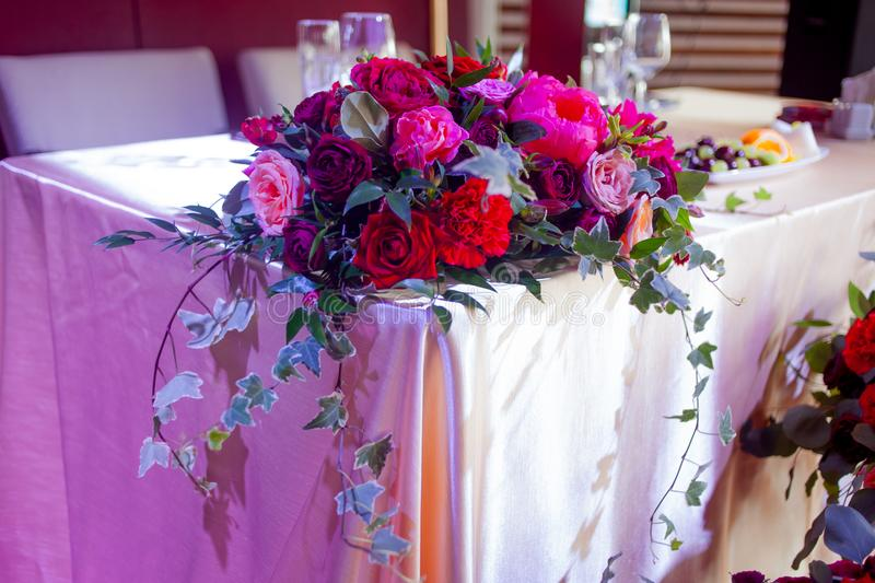 Wedding decor. Red Flowers in the restaurant, table setting royalty free stock photography