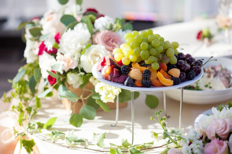 Wedding decor. Flowers in the restaurant, food on the table stock photo