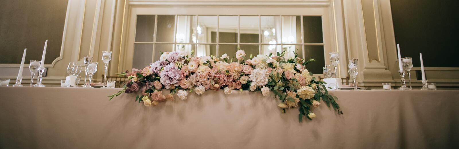 Wedding decor. Fresh bouquets of flowers on the table of the bride and groom at the restaurant.  royalty free stock photo