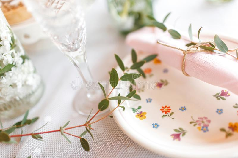 Wedding table decorated with napkins and flowers. The wedding table is decorated with napkins and flowers and olive branches royalty free stock images
