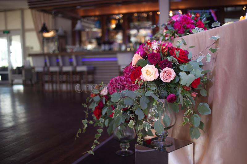 Wedding decor. Red Flowers in the restaurant, table setting royalty free stock image