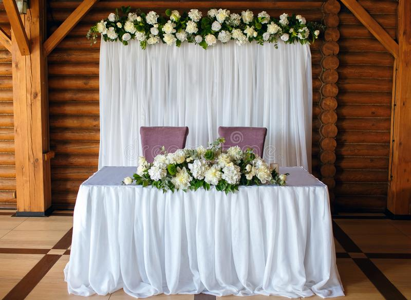 Wedding decor of the restaurant, the table of the newlyweds on a wood background, beautifully decorated decor stock photography