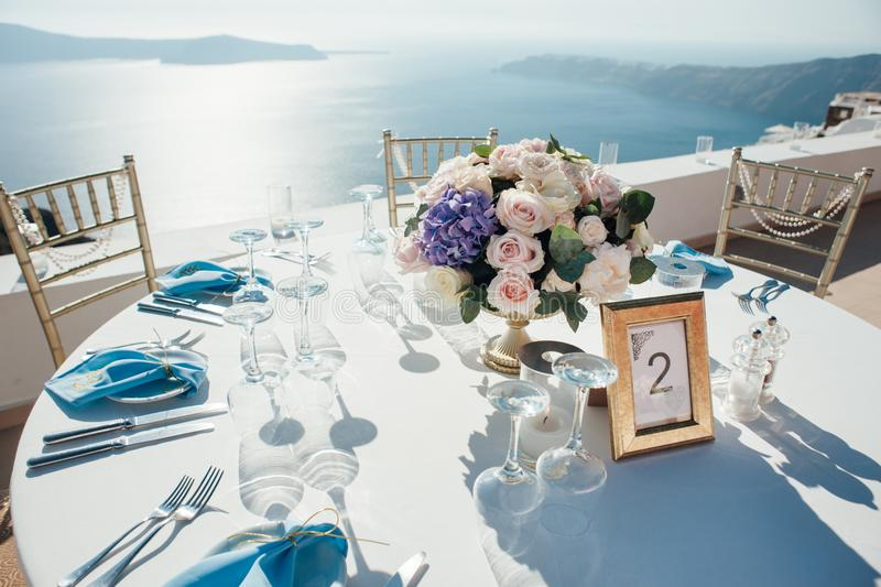 Wedding decor of tables on the island of Santorini in gold, blue and white colors royalty free stock image