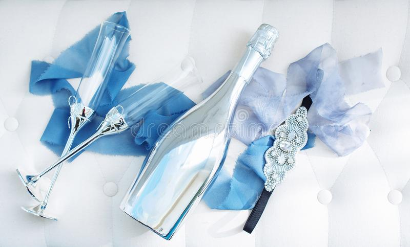 Wedding decorated glasses and champagne bottle on table. Wedding decorated glasses and platinum champagne bottle on table with silk blue stripes and jewerly stock photography