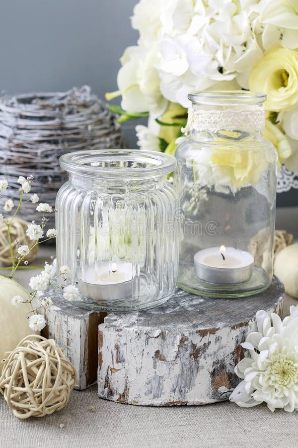 Wedding decoration with flowers and candles in glass jars royalty free stock images