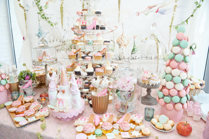 Wedding decoration with pastel colored cupcakes, meringues, muffins and macarons royalty free stock image