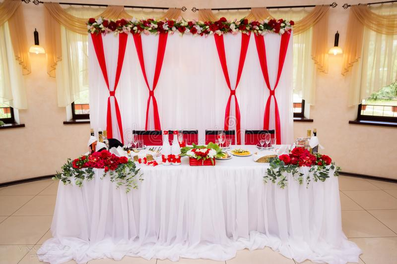 Wedding decorations of white and red color on table for newlyweds. Marriage celebration banquet hall. stock photography