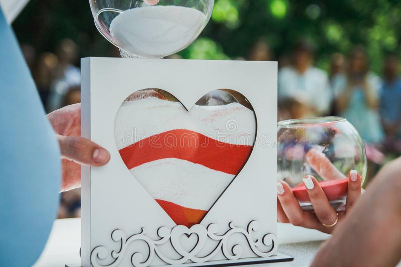 Wedding decorative heart for ceremony. Red and white sand in the glass and wooden form. bride and groom hands with golden rings. stock photo