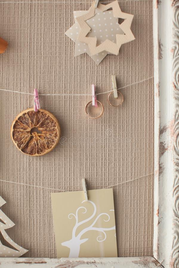 Wedding designer decor in the form of a frame with rings, beads, a bow of satin ribbon, dried orange slice and cut out pictures. stock photography