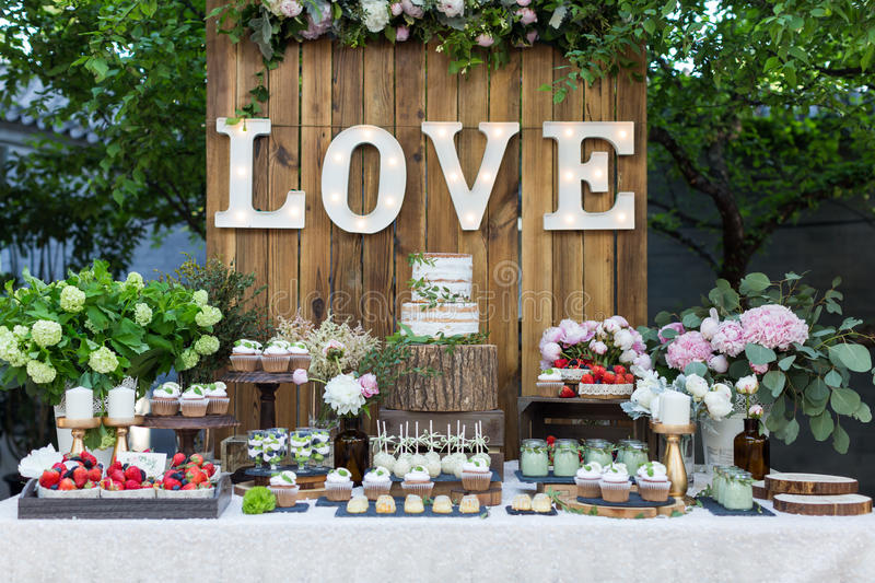 Wedding dessert area. Tiered wedding cake and cupcakes at outdoor wedding party royalty free stock photo
