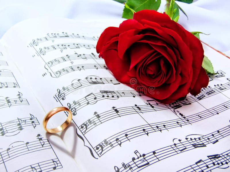 Wedding detail. Sheet music of the Wedding March with roses and rings stock photography