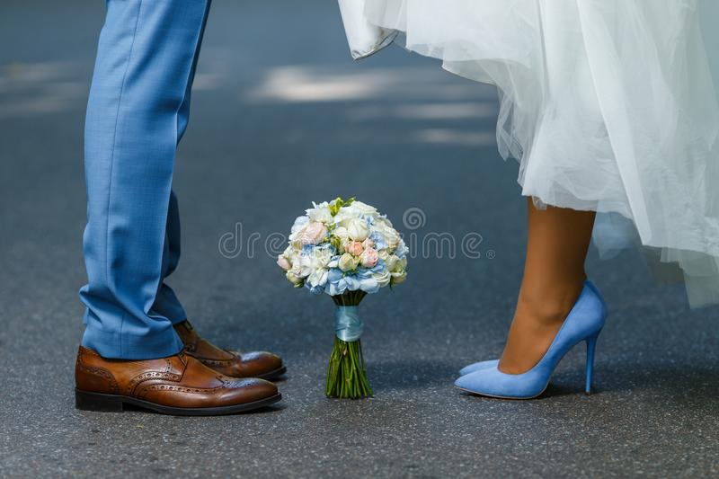 Wedding details: classic brown and blue shoes of bride and groom. Bouquet of roses standing on the ground between them. Newlyweds stock photo