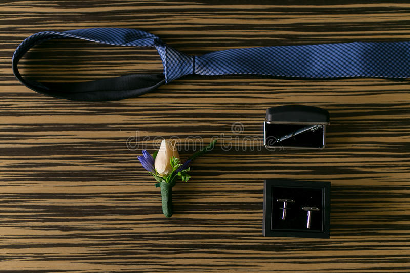 Wedding details. Groom accessories. Cufflinks, tie and boutonniere on table stock photo
