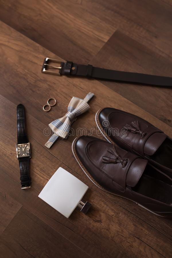 Wedding details. Groom accessories. Shoes, rings, belt, and bowtie stock image