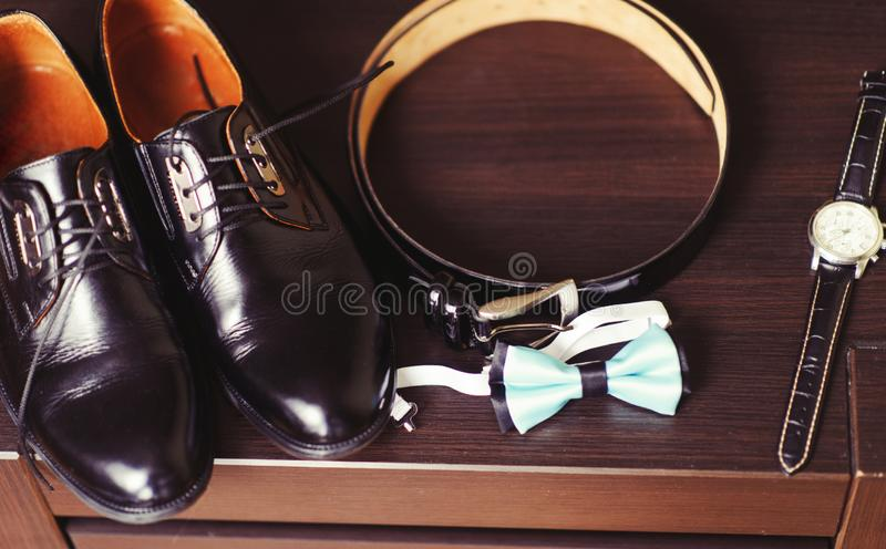 Wedding details. Groom accessories. Shoes, rings, belt, and bowtie stock photo