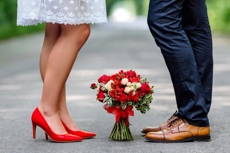 Wedding details: stylish red and brown shoes of bride and groom. Bouquet of roses standing on the ground between them. Newlyweds s stock photos