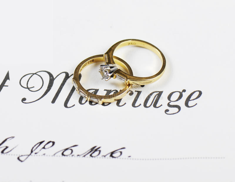 Wedding and diamond engagement rings on marriage certificate. Closeup macro stock images