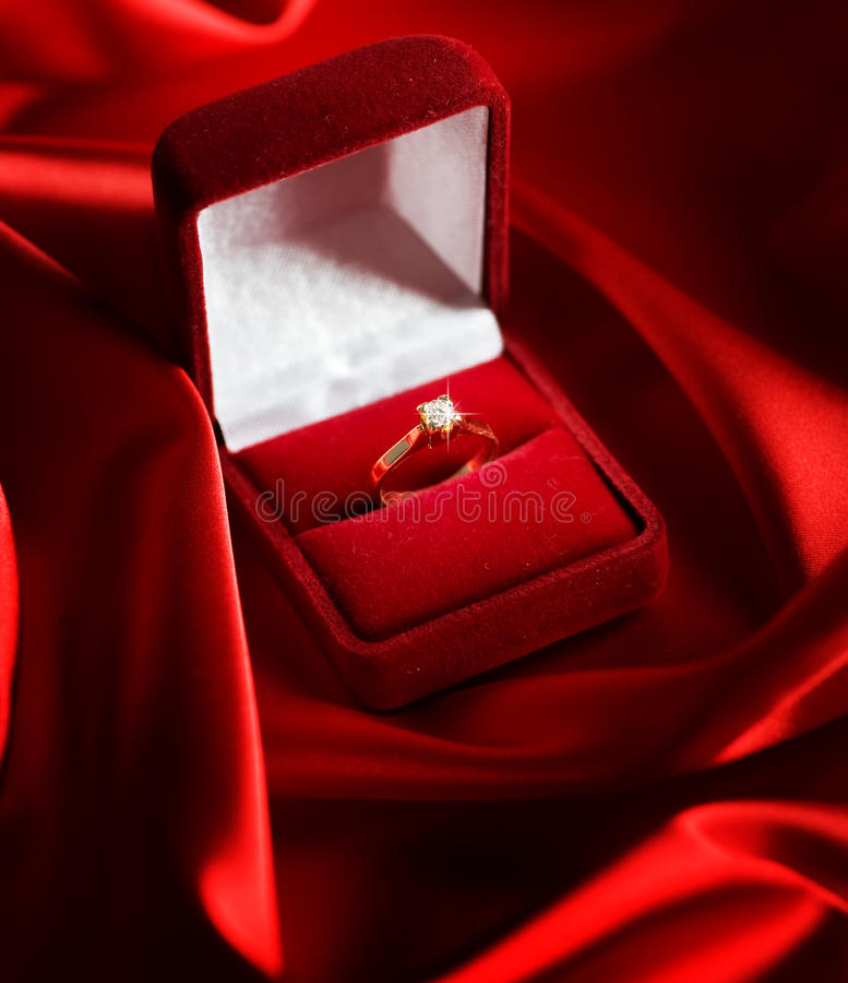 Wedding Diamond Ring. Beautiful Wedding Ring over Red Silk Background