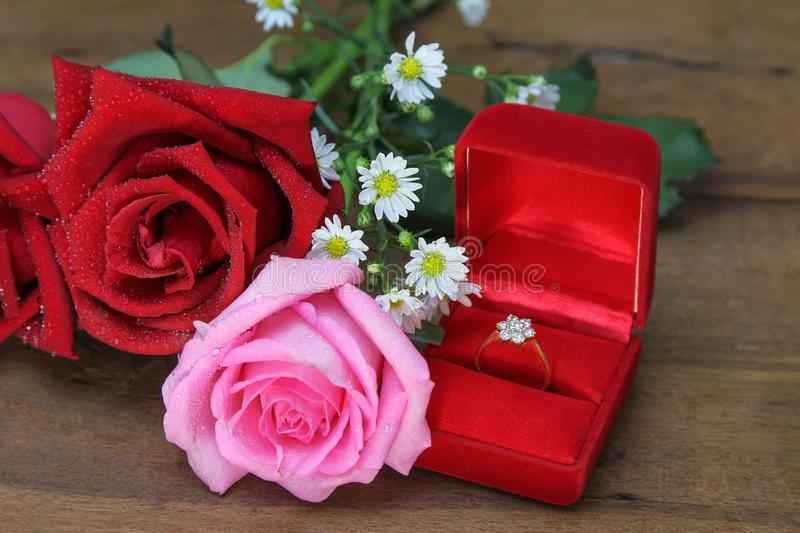 Wedding bouquet from pink and red roses, Wedding ring in a red box on wooden background. stock photos