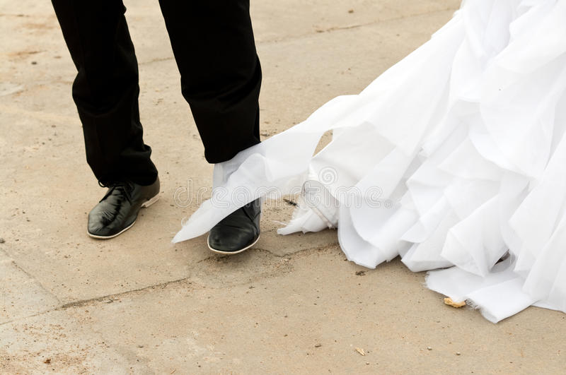 Wedding disaster. Concept - groom stepped into bride dress, tearing it with his shoe royalty free stock photography