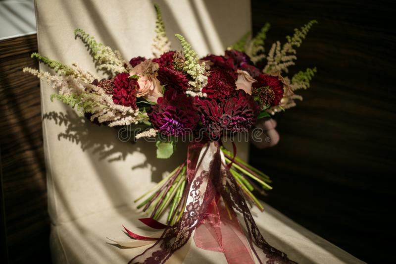 A wedding disheveled bouquet with burgundy dahlias and cream-colored roses with ribbons stands on a chair, lit by the sun. stock image