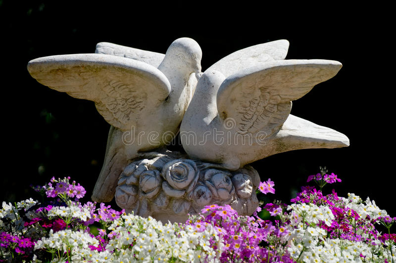 Wedding Doves. Two wedding doves made of concrete and kissing each other and beautiful flowers at the bottom. The doves are in a black background stock photography