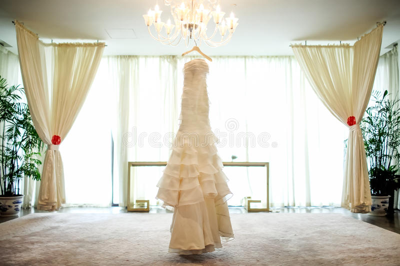 Wedding dress. Hanging on the chandelier stock photography