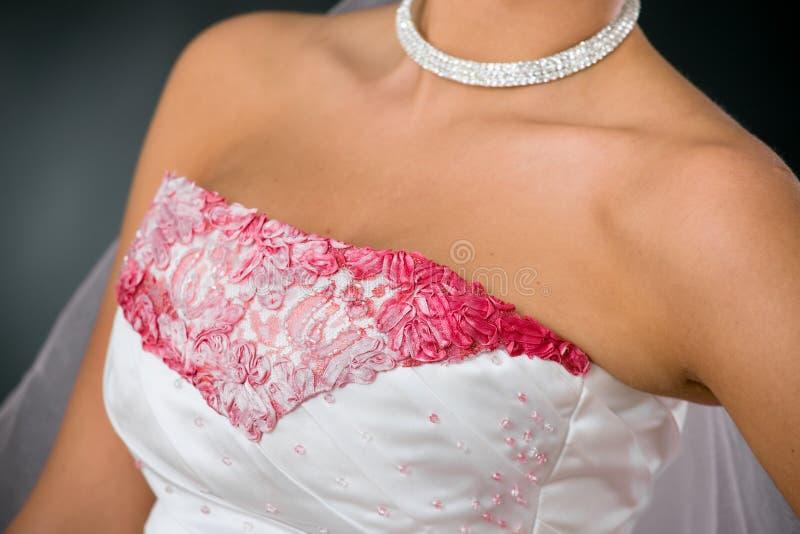 Wedding dress closeup. Closeup photo of wedding dress, with pink embroidery and beads royalty free stock photos